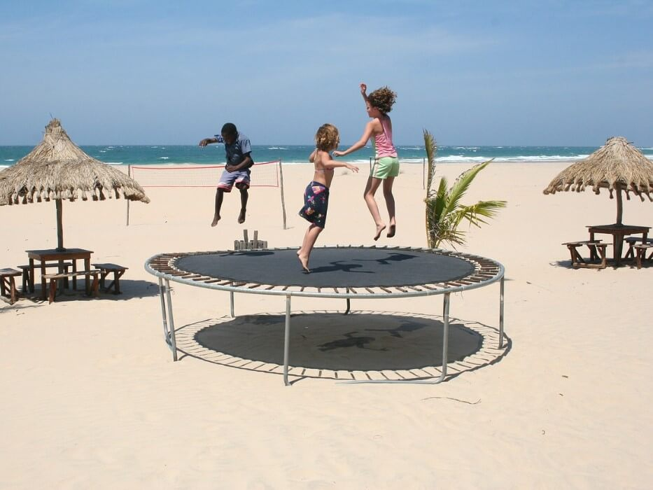 3 children jumping on a trampoline on the beach